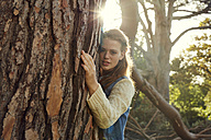 Portrait of young woman hugging tree  at backlight - SRYF00431