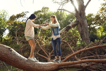 Two young woman balancing on tree trunk - SRYF00440