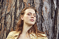 Portrait of redheaded young woman leaning against tree trunk with eyes closed - SRYF00452