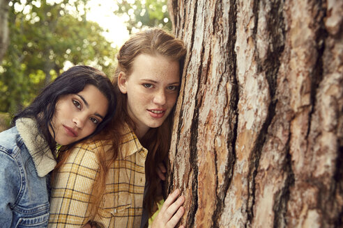 Portrait of two young women leaning against tree trunk - SRYF00458