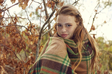 Portrait of redheaded young woman wrapped in blanket in autumnal nature - SRYF00464