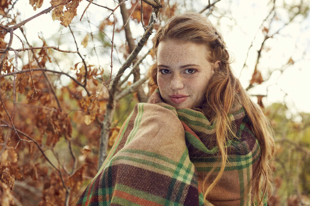 Portrait of redheaded young woman wrapped in blanket in autumnal nature - SRYF00464 - Martina Ferrari/Westend61