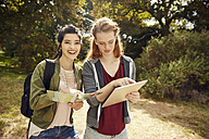 Two young women with tablet and map in nature - SRYF00482