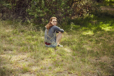 Portrait of young woman sitting on a meadow - SRYF00488