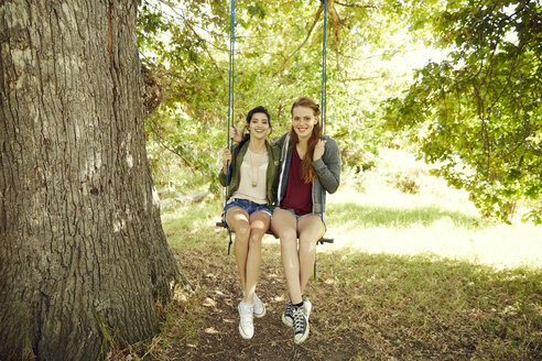 Two best friends sitting together on a swing - SRYF00494
