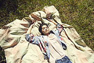 Young woman lying on blanket listening music with headphones - SRYF00497