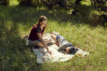 Two friends relaxing on blanket on a meadow - SRYF00503
