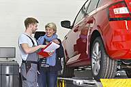 Car mechanic with client in workshop at car - LYF00692