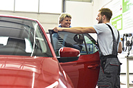 Car mechanic with client in workshop at car - LYF00695