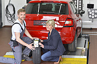 Portrait of smiling car mechanic with client and tyre in workshop at car - LYF00698