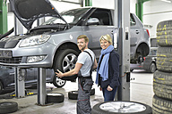 Portrait of smiling car mechanic with client in workshop at car - LYF00701
