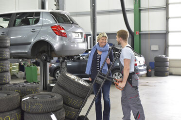 Car mechanic with client and tyres in workshop - LYF00704