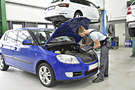 Car mechanic in a workshop using diagnostics computer at car - LYF00710
