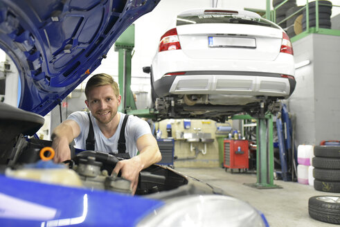Car mechanic in a workshop examining car - LYF00713