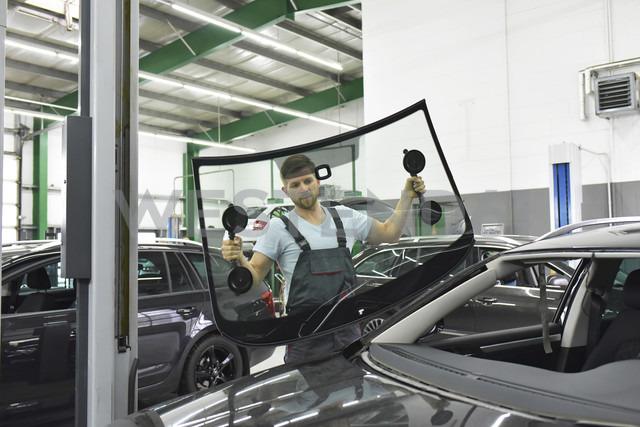 Car mechanic in a workshop changing car window - LYF00716