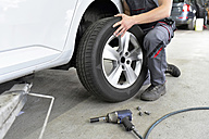 Car mechanic in a workshop changing car tyre - LYF00719