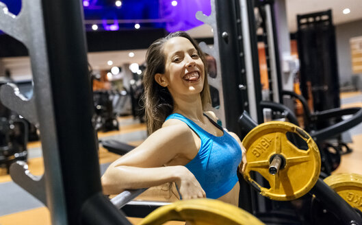 Happy young woman after work out in the gym - MGOF03266