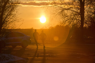Silhouette of two joggers in winter at sunset - KNTF00845