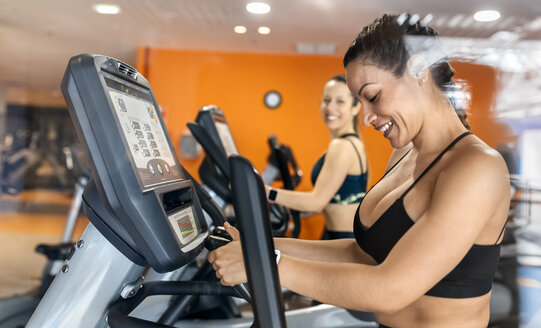 Two women working out in gym using an elliptical trainer - MGOF03270