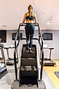 Young woman training in gym with a stairs machine - MGOF03273