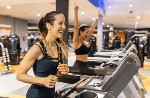 Two happy women working out in gym on a treadmil - MGOF03276