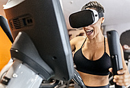 Woman wearing VR glasses on an elliptical traine in the gym - MGOF03294