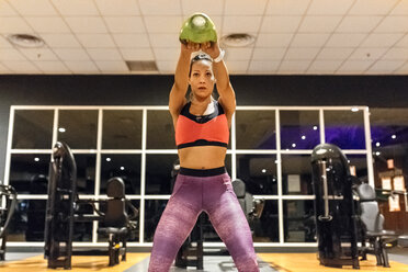 Woman lifting kettlebell in gym - MGOF03300