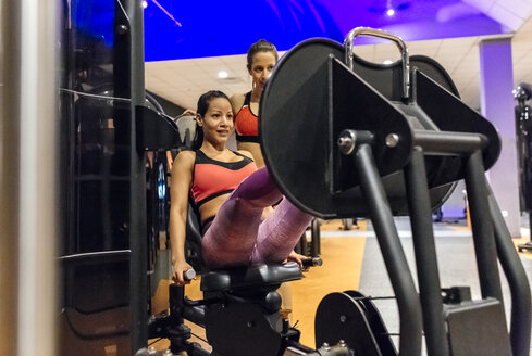 Woman with her trainer working out in gym - MGOF03309