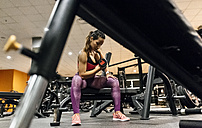Woman lifting dumbbell in gym - MGOF03315