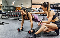 Woman with her trainer working out in gym - MGOF03318