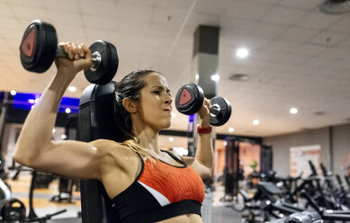 Woman lifting dumbbells in gym - MGOF03321