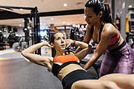 Woman with her trainer working out in gym - MGOF03324