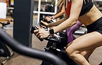 Close-up of woman on spinning bike in the gym - MGOF03327