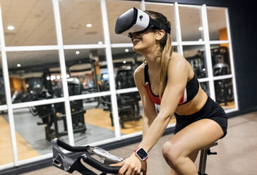 Woman with VR glasses on spinning bike in the gym - MGOF03330