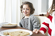 Portrait of smiling little girl at dining table - FSF00835