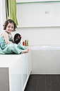 Portrait of smiling little girl with hand mirror sitting in bathroom - FSF00847