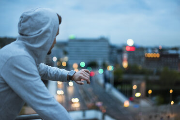 Athlete checking his smartwatch above the city at dawn - DIGF02397