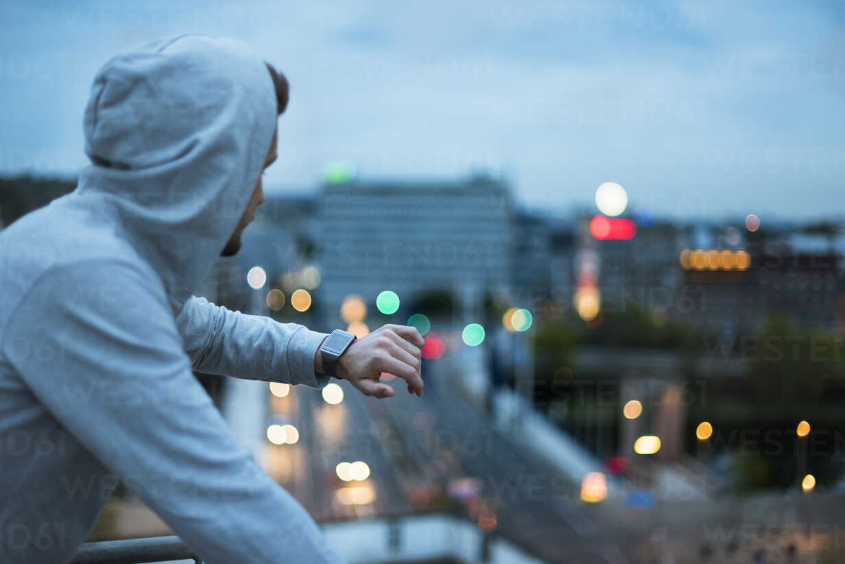 Athlete checking his smartwatch above the city at dawn - DIGF02397 - Daniel Ingold/Westend61
