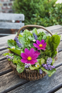 Edible flowers, leaves and herbs in wickerbasket on garden table - GWF05192