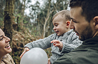 Happy family playing with a balloon in forest - DAPF00726