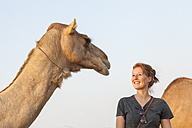 UAE, happy woman looking at a camel - MMAF00086