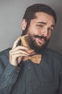 Man combing his beard with a wooden comb, wearing denim shirt and cork bow tie - RTBF00834