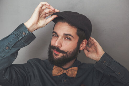 Bearded man putting on his cap, wearing denim shirt and cork bow tie - RTBF00837