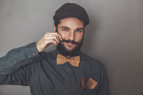 Portrait of bearded man wearing cap, denim shirt, cork bow tie, wearing wooden combs for beard and mustache in his pocket - RTBF00840