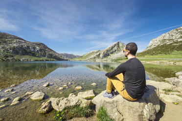 Spain, Asturias, Picos de Europa National Park, man sitting at Lakes of Covadonga - EPF00443