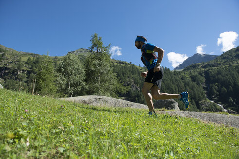 Italy, Alagna, trail runner on the move near Monte Rosa mountain massif - ZOCF00259