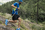 Italy, Alagna, trail runner on the move over rocks in forest - ZOCF00265