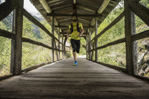 Italy, Alagna, man running on wooden bridge in the mountains - ZOCF00268