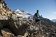 Italy, Alagna, trail runner on the move near Monte Rosa mountain massif - ZOCF00274