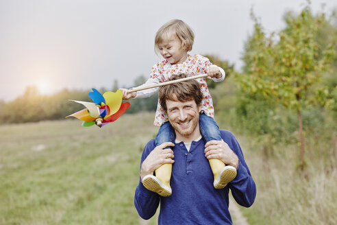 Father carrying daughter with pinwheel on shoulders - RORF00839